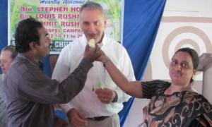 Anil & Florence Kumar presenting birthday cake to Steve Hogan
